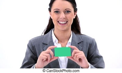Happy brunette holding a business card against a white...