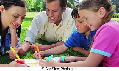 Smiling family coloring together