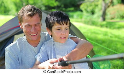 Smiling father and son fishing together in the countryside