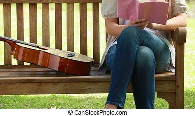 Woman reading a book with a guitar next to her on a bench