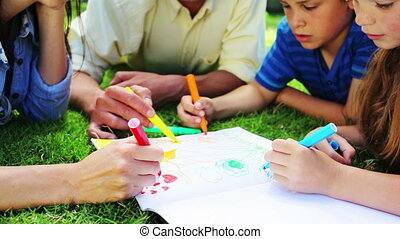 Happy children drawing with their parents in a parkland