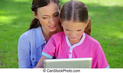 Smiling mother and daughter using a tablet computer