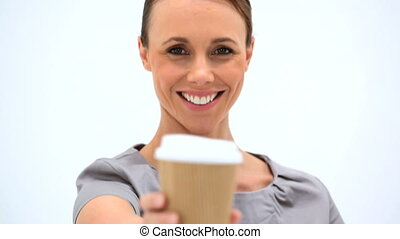 Smiling woman holding a cup of coffee against a white...