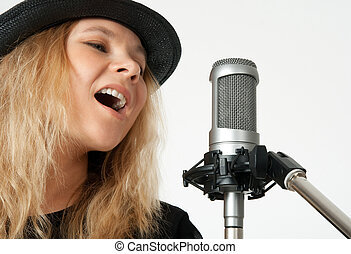 Young woman singing with studio microphone - Young woman in...