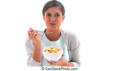 Smiling woman eating a fruit salad against a white...
