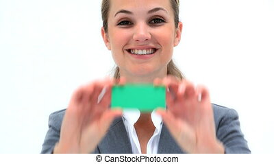 Smiling woman showing a business card against a white...