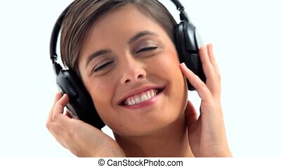 Smiling brunette wearing headphones against a white...