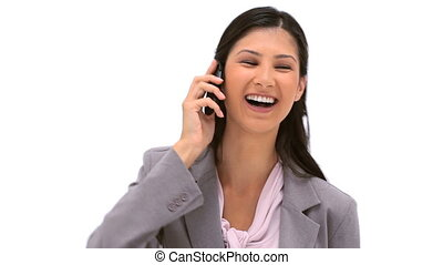 Smiling brunette woman using her cellphone against a white...