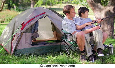 Father and son fishing while sitting near their tent
