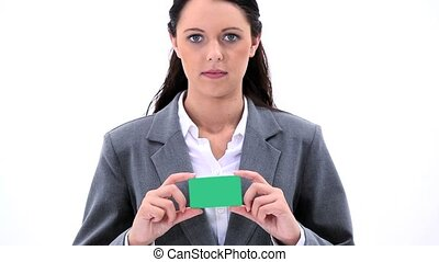 Smiling brunette woman holding a business card against a...