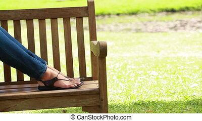 Woman reading a book while sitting in a park