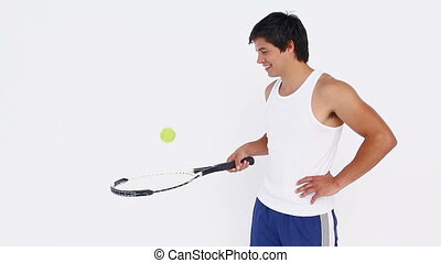 Man does rebounds with a tennis ball on a racket against...