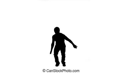 Silhouette of a man spinning as he jumps in slow motion