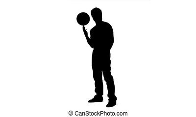 Silhouette of a man balancing a ball on his finger in slow motion