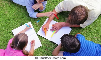 Family drawing together while lying in a park