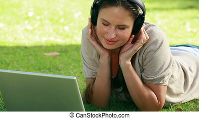 Woman wearing headphones while using a laptop
