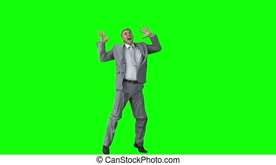 Businessman in slow motion raising his arms against a green...