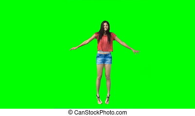 Woman performing a jumping jack against a green background