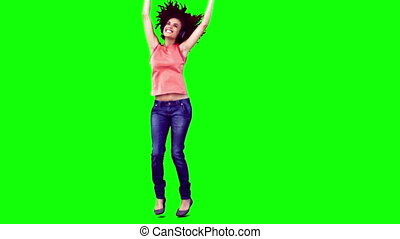 Happy woman in slow motion dancing against a green...