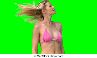 Blonde shakes her head against a green screen
