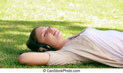 A woman is lying on grass while listening to music