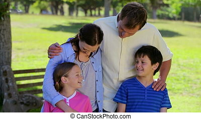 Smiling family standing upright together in a park