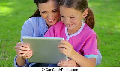 Smiling woman using a tablet pc with her daughter while...