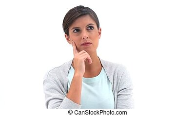 Thoughtful brunette woman standing upright against a white...
