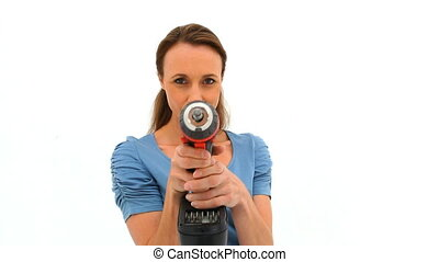 Brunette woman playing with a drill against a white...