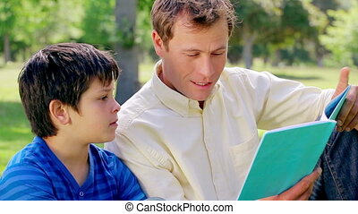 Smiling man reading a book with his son in a parkland