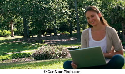Woman laughing while using a laptop