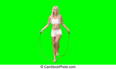 Blonde skipping over a rope against a green screen