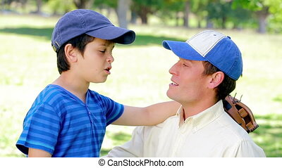 Father and son wearing baseball caps in a park