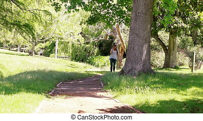 Woman talking on the phone while walking in a park