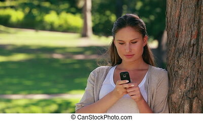 Woman leaning against a tree is holding a mobile phone