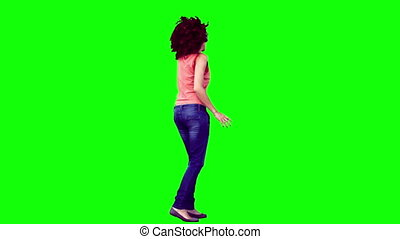 Woman in slow motion listening to music against a green...
