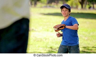 Smiling boy playing baseball while standing upright in the...