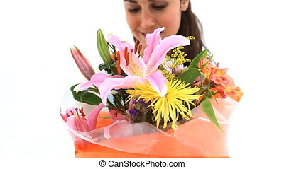 Smiling woman holding a bunch of flowers against a white...