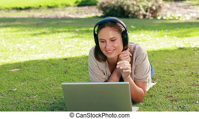 Woman using a laptop is listening to music