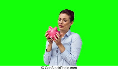 Brunette in slow motion holding a piggy bank against a green...