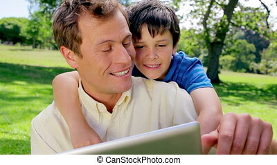Happy father and son using a tablet computer in a park