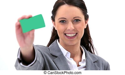 Smiling brunette holding a business card against a white...