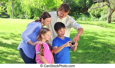 Little boy using a digital camera with his family in a park