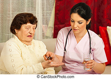 Doctor gives pills to senior woman