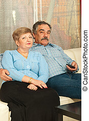 Middleaged couple watching tv home - Middle aged couple...