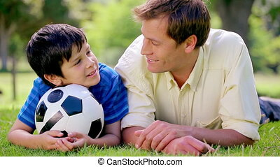 Happy father and son lying on the grass with a soccer ball