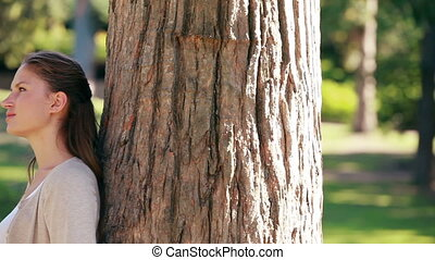 Smiling woman leaning against a tree in a park