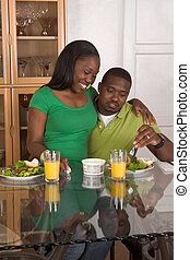 Young ethnic couple by table eating breakfast - Young black...
