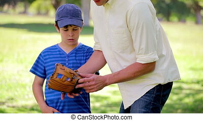 Little boy wearing a baseball glove in the countryside