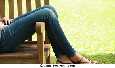 Woman lying on a bench in a park